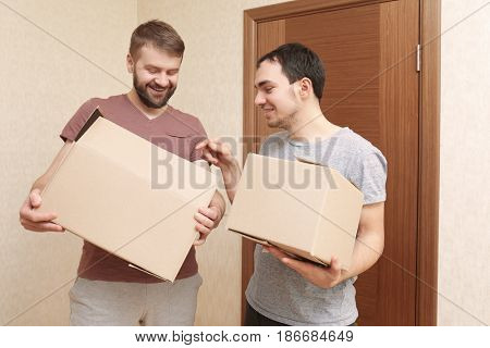 Gay couple unpacking cardboard boxes at home