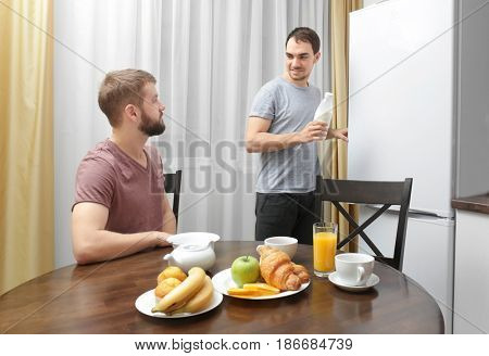 Happy gay couple having breakfast in kitchen