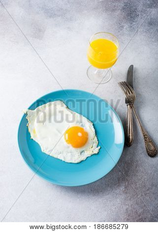 Fried egg on blue plate and orange juice. Healthy breakfast concept with copy space.