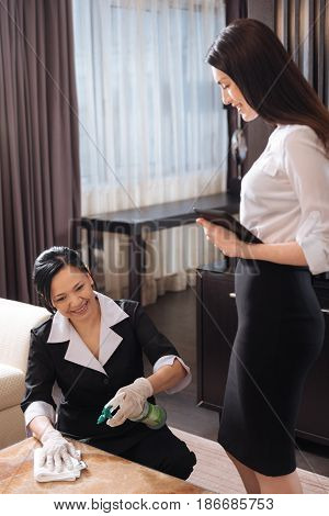 Housekeeping manager. Attractive professional hotel manager standing near the chamber maid and looking at her while controlling her work