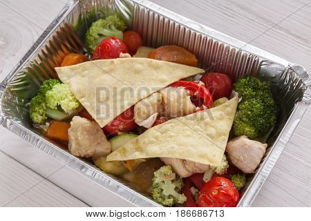 Healthy food, diet top view. Lunch box with Weight loss nutrition closeup. Flatbread and salad with tomatoes