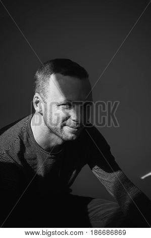 Man Sitting In Shadow Under Small Sunlight Beam