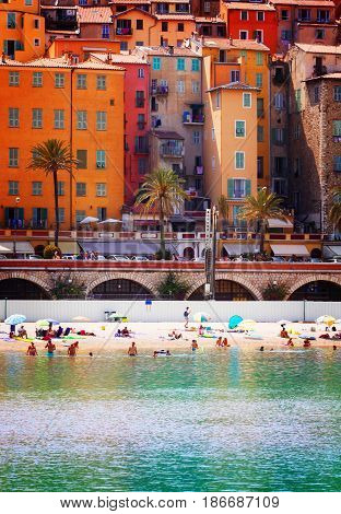 colorful houses of Menton old town with beach and sea water, France, retro toned