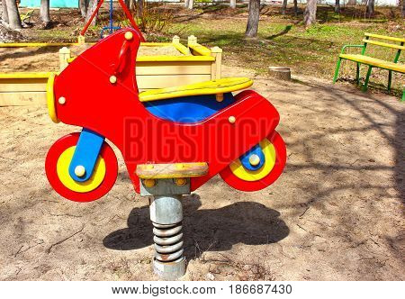 Red motorcycle, children's playground in the spring, a swing