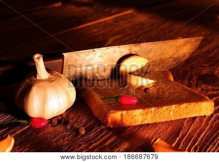 Rural still life spices, onion, garlic, pepper, knife, against the background of an old wooden table