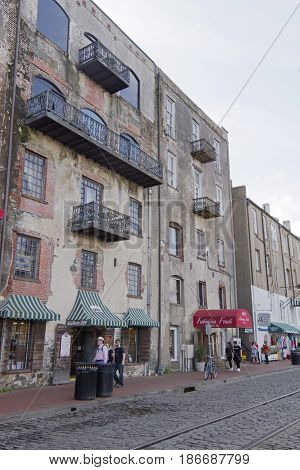 Savannah, Georgia, USA - January 20, 2017: People walking along River Street in Savannah, Georgia with its historical wrought iron balconies cobblestone streets and artful architecture