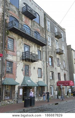 Savannah Georgia USA - January 20 2017: People walking along River Street in Savannah georgia with its historical wrought iron balconies cobblestone streets and artful architecture