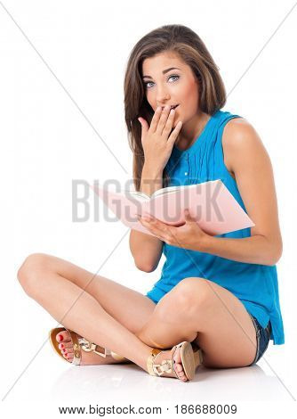 Beautiful student teen girl with book sitting on floor, isolated on white background