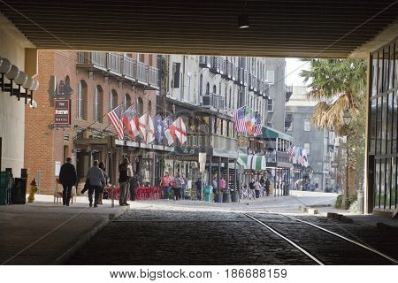 Savannah Georgia USA - January 20 2017: Historic River Street along the Savannah River viewed from the tunnel passageway that divides it. Also called River Street Home the Riverwalk is a popular destination for locals and tourists with its cobblestone str