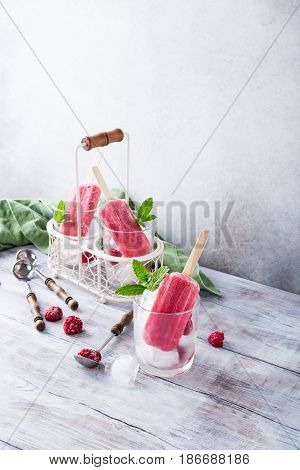 Homemade raspberry popsicles in glass with ice, raspberries and mint on old white wooden table.. Healthy summer food concept with copy space.