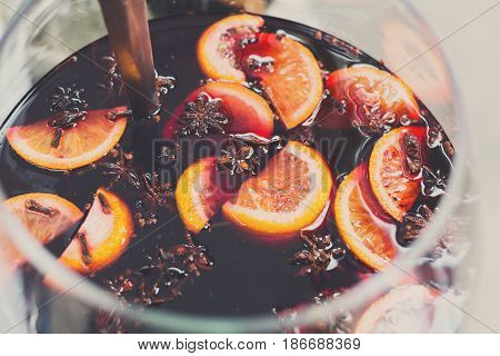 Making hot alcohol, mulled wine for sale at country fair. Glintwine from red wine with citrus and cloves in big metal stock pot, mixed with soup ladle. Closeup