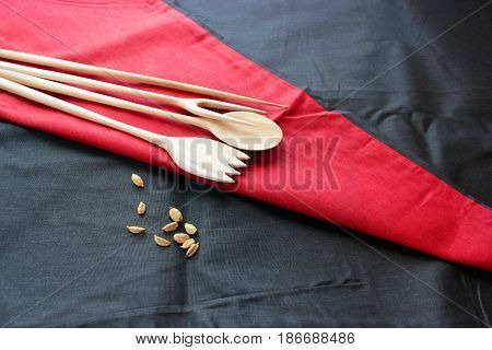 Spices  for cooking . On a red, black,  cloth background . Next to a wooden spoon