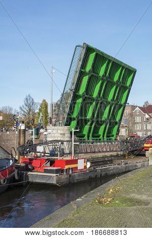 Old boat and modern green drawbridge in the day in Amsterdam