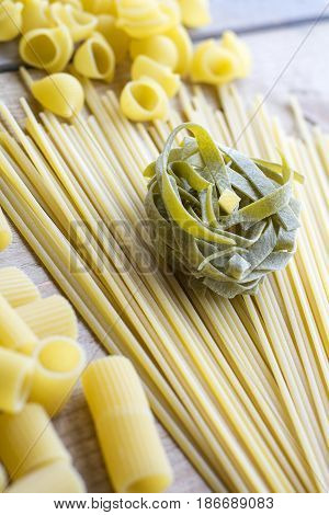Green raw pasta is on the yellow linguini