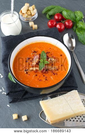 Thick tomato soup with basil and fried bacon in a black ceramic bowl on a grey abstract background. Healthy eating concept Fresh tomato soup with creme fraiche