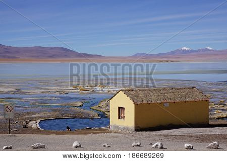 Beautiful pastel colored natural landscape of a lake and natural thermal pool with a yellow hut in foreground