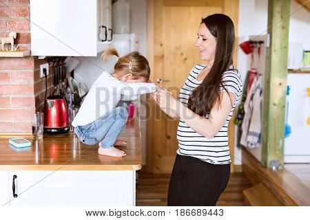 Beautiful young mother at home and her cute little daughter crouching on kitchen countertop, ready to jump.