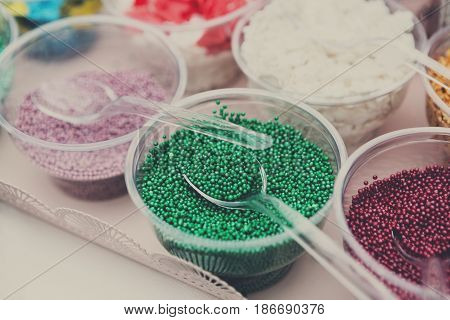 Ice cream treats and toppings sale. Rainbow sprinkles, stars, non pareil and glitter cupcake decorations, bright green. Closeup in plastic plates with spoons. Confectionery store