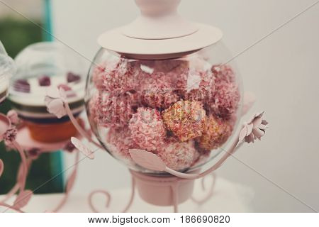Confectionery sale. Cconut candies or cakes, pink balls in glass jar closeup