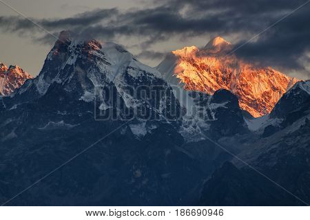 Beautiful first light from sunrise on Mount Kanchenjugha Himalayan mountain range Sikkim India. Orange tint on the mountains at dawn
