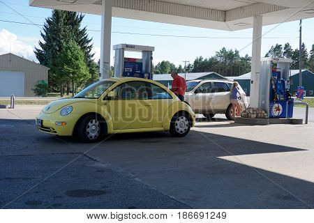 HARBOR SPRINGS, MICHIGAN / UNITED STATES - AUGUST 5, 2016: Motorists fill their gas tanks with Mobil gasoline at the E-Z Mart convenience store in Harbor Springs.
