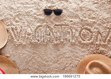 The word vacation written in a sandy tropical beach