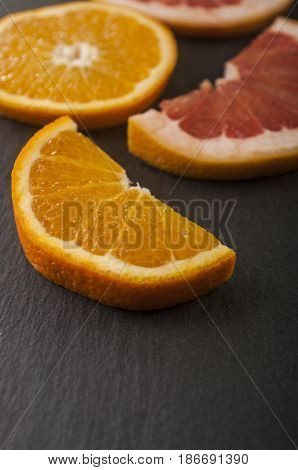 Orange and grapefruit close up on dark background