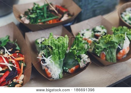 Street food festival, catering service. Vegetable salads in kraft paper plates sold outdoors at local market place, shallow depth of field