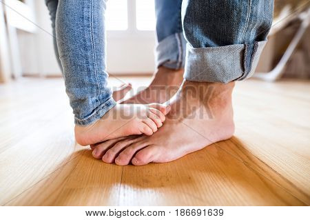 Beautiful young family. Close up of bare feet of little girl standing on feet of her father.