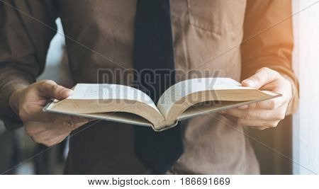 Businessman standing near window and reading book vintage tone.