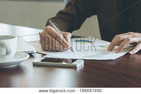 Businessman analyzing graph document with laptop and coffee in office.