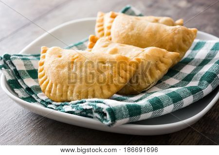Delicious typical Spanish empanadas on wooden table