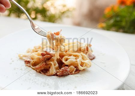 Eating pasta. Italian carbonara with bacon, egg and parmesan decorated with basil on white round plate at wooden table. Restaurant food, selective focus