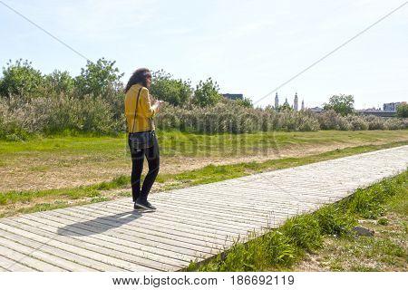 Woman Walking In A Park In Front Of El Pilar, Zaragoza