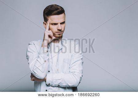 Focused serious man standing in front of camera. Attractive guy holding his right hand at forehead and deeply thinking about something. Isolated. Close up