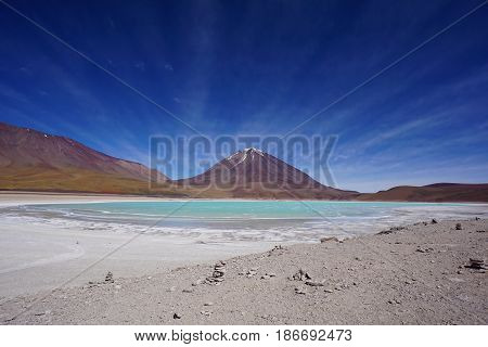 Landscape photo of an aquamarine colored lake in front of a snow capped mountain in the high altitude of Southern Bolivia
