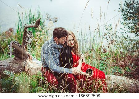Couple drinking tea in the forest sitting on the grass