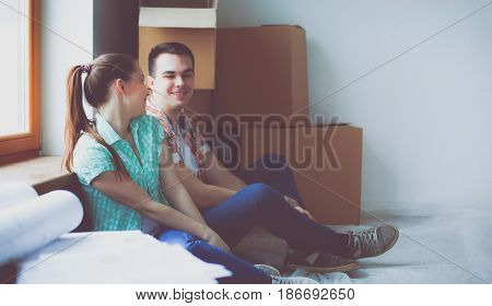 Couple moving in house sitting on the floor