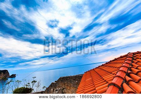 Wide angle view from the roof of red tiles to landscape. Dramatic sky with storm clouds over sea. Bird's eye view.
