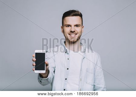Smiling stylish young man with beard in a white jeans shirt holding mobile phone and standing in front of the camera. Close up. Isolated