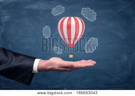 A businessman's hand turned up and a small air balloon hovering above it on chalkboard background. Travelling business. Air travel for all. Work overseas.