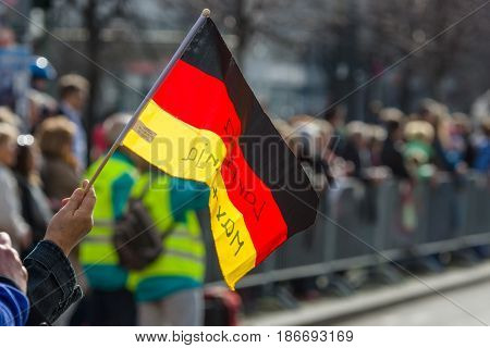 BERLIN - APRIL 03 2016: The annual Berlin Half Marathon. Spectator's hand holding a flag of Germany.