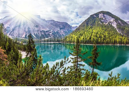 Sunshine on a cloudy day.  Magnificent lake in South Tyrol, Italy. The concept of walking and eco-tourism. Water reflects the surrounding mountains and forest