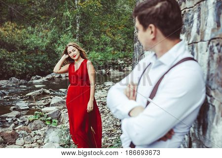 Couple is standing in the nature, the guy in front