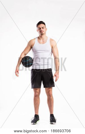 Young handsome fitness man in white sleeveless shirt holding medicine ball. Studio shot on white background.