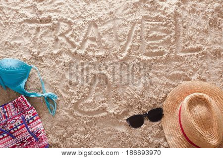 The word Travel written in a sandy tropical beach