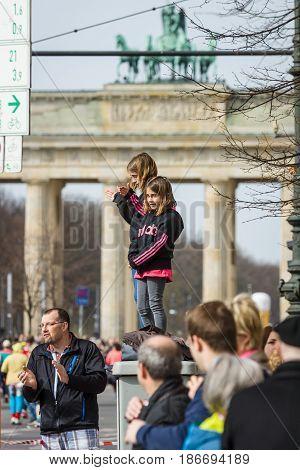 BERLIN - APRIL 03 2016: The annual Berlin Half Marathon. Two girls watching a marathon against the backdrop of the Brandenburg Gate.
