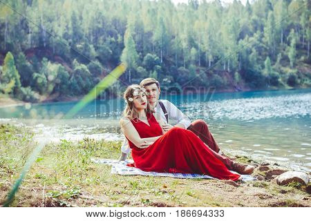 Couple sitting on the nature by the lake on the ground