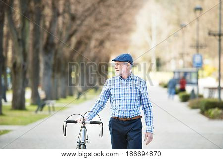 Handsome senior man in blue checked shirt with bicycle in town. Sunny spring day.