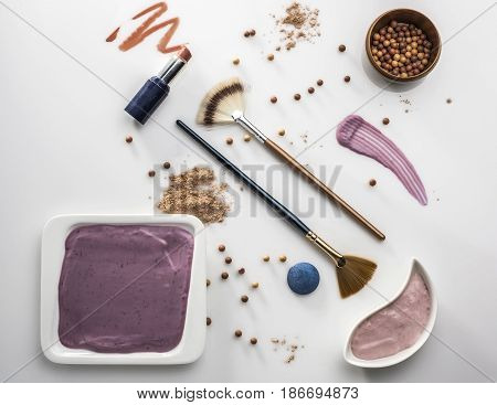 crushed decorative cosmetics nude on white background top view
